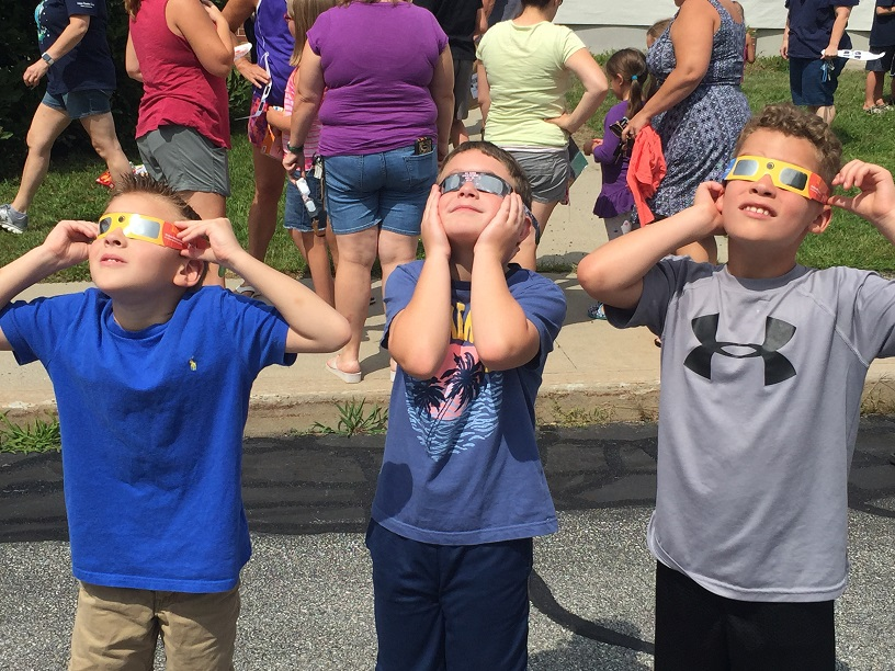 three children with eclipse glasses