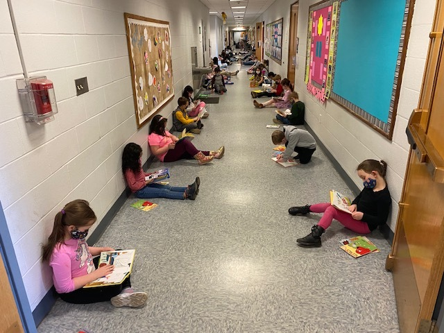 Students sitting in the hallway reading