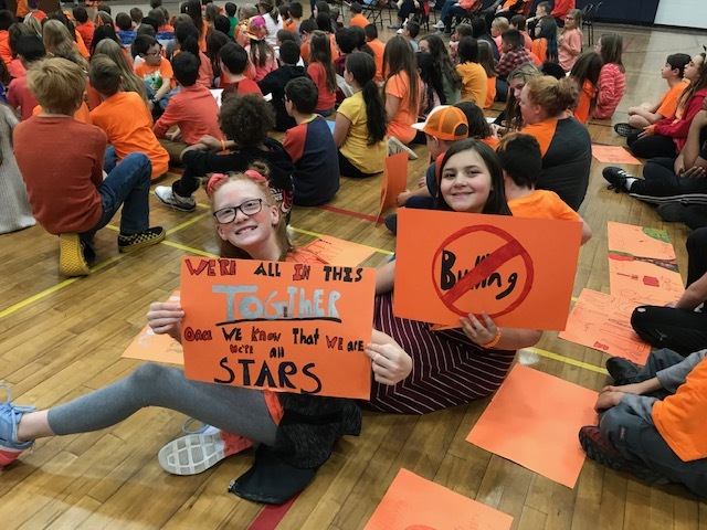 2 Student Council Members holding a sign