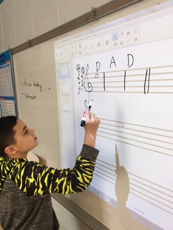 kids writing music notes on board