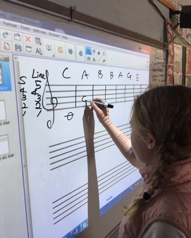 another student writing music notes on board