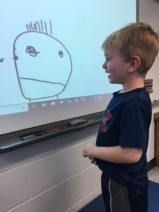 boy drawing picture on smartboard