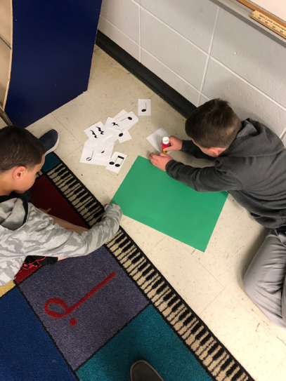students working on floor in music class
