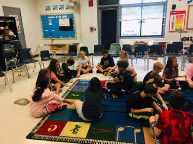 students on rug in music class
